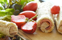 Bread stuffed pork bologna roll with cut strawberry and vegetable on chop block Stock Images