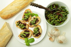 Bread with sundried tomatos and green bean. Angle view on bruschettas with sundried tomatos and green bean with garlic and basil for vegetarians Stock Photo