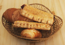 Bread and sweet pies in basket Stock Photography