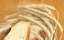 Bread on the table. Bread slices with ears of wheat on the table Royalty Free Stock Photos