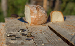 Bread on a table with coins and knife. Defocused Royalty Free Stock Photography