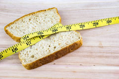 Bread with tape measure on wooden surface Royalty Free Stock Photos