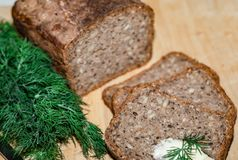 Bread. Tasty, home made, baked, wholegrain, wholemeal, brown bread. with chopped dill, butter and knife on the wooden board. Polis Royalty Free Stock Images
