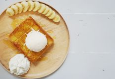 Bread toast with ice cream, banana slices and whipped cream in wooden plate. Bread toast with ice cream, banana slices and whipped cream royalty free stock image