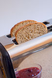 Bread in toaster. Two slices of whole wheat bread in toaster stock photos