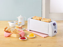 Bread toaster and breads Stock Images