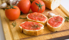 Bread with tomato. Slices of bread with a tomato paste, parsley and tomatoes on a kitchen board Royalty Free Stock Images