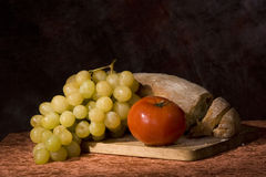 Bread, tomato and grapes. A bunch of white grapes, a bread and a tomato on a wooden board Stock Image