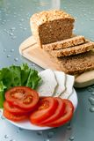 Bread, tomatoes and cheese. Wholegrain bread on the board, tomatoes, salad and cheese Royalty Free Stock Photos