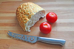 Bread, tomatoes and knife2. Bread and bread crumbs,tomatoes and tomatoe knife on a wooden worktop Royalty Free Stock Photos
