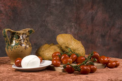 Bread, tomatoes and mozzarella. Still life of bread loaves, vines with red tomatoes, buffalo mozzarella on a plate and a pitcher of wine Royalty Free Stock Image