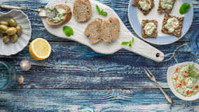 Bread with tzatziki on the blue wooden table with accessorize horizontal. Bread with tzatziki on the blue wooden table with olives  , lemon and tableware top Stock Image
