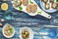 Bread with tzatziki on the blue wooden table with accessorize. Bread with tzatziki on the blue wooden table with olives  , lemon and tableware top view Stock Photos