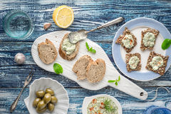 Bread with tzatziki on the blue wooden table with accessorize top view. Bread with tzatziki on the blue wooden table with olives  , lemon and tableware top view Stock Photo