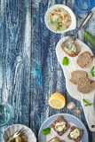 Bread with tzatziki on the blue wooden table with accessorize vertical. Bread with tzatziki on the blue wooden table with olives  , lemon and tableware top view Stock Image