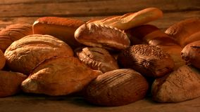 Bread variety still life. Assortment of fresh organic bread on vintage wooden surface. Bakery and healthy eating stock video footage