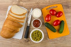 Bread, vegetables on cutting board, kitchen knife, mayonnaise an Royalty Free Stock Photos