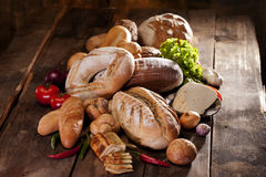 Bread and vegetables near bread. Sliced cheese near vegetables and bread on wood table Royalty Free Stock Photo