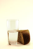 Bread and water 2. Glass of water and bread isolated against white background royalty free stock photos