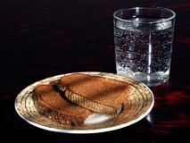 Bread and water. Simple still-life: plate with black bread and glass of water royalty free stock images