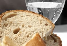 Bread and Water. Sliced bread with a glass of mineral water in the background Royalty Free Stock Photos