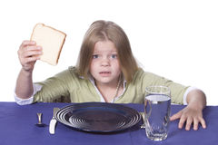 Bread and Water Dinner. Young girl in disbelief about her bread and water dinner Royalty Free Stock Images
