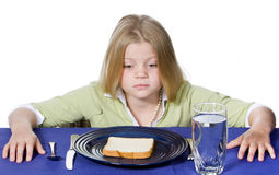 Bread and Water Dinner. Young girl in disbelief about her bread and water dinner Stock Photo