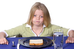 Bread and Water Dinner. Young girl showing unhappy acceptance of her bread and water dinner Stock Photo