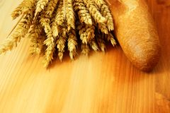 Bread and wheat. Bread and raw wheat on top of the wooden table Stock Images