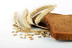 Bread and wheat. Rye bread and corn ears on white Royalty Free Stock Images