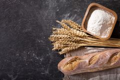 Bread with wheat ears on dark board. Top view stock photos