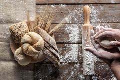 Bread with wheat ears and flour on wood board, top view royalty free stock image
