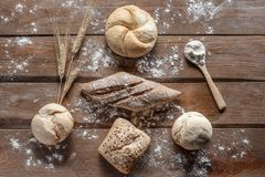 Bread with wheat ears and flour on wood board, top view stock image