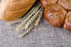 Bread and wheat ears lying on sacking Royalty Free Stock Image