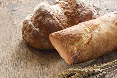 Bread on old wooden background. Bread with wheat ears on old wooden background Royalty Free Stock Photography