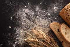Bread wheat and flour on black table top view. Bread wheat and flour on black table elevated. Top view. Horizontal composition stock photos