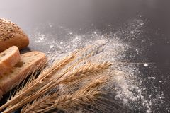 Bread wheat and flour on black table elevated. Elevated view. Horizontal composition stock image