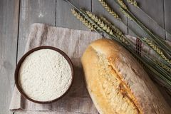 Bread wheat spike and flour on wooden background. The bread wheat spike and flour on wooden background Stock Photos