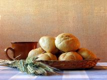 Bread and wheat still-life. Bread loaves, mugful of drink and wheat straws on the table Stock Images