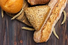Bread and wheat on white wooden background. top view with copy space.  royalty free stock image