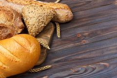 Bread and wheat on white wooden background. top view with copy space.  stock image