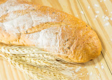 The bread and wheat on the wood background, warm toning Stock Photography