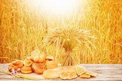 Bread and wheat on the wooden table Stock Photos