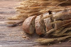 Bread and wheat on wooden table, shallow DOF Royalty Free Stock Image