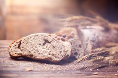 Bread and wheat on wooden table, shallow DOF Royalty Free Stock Photos