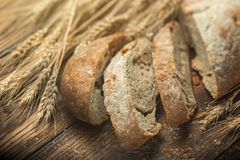 Bread and wheat on wooden table, shallow DOF Stock Images