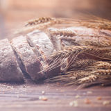 Bread and wheat on wooden table, shallow DOF Royalty Free Stock Photo
