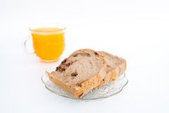 Bread on a white plate and glass of orange juice. Isolated on white. Stock Photo