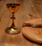 Bread and wine. Cup of red wine and broken bread on pine table Royalty Free Stock Photos