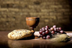 Bread and wine. Grapes, wheat, bread and wine in a wood table royalty free stock image